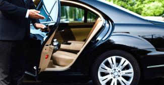 Un chauffeur de VTC ouvrant la porte de la voiture